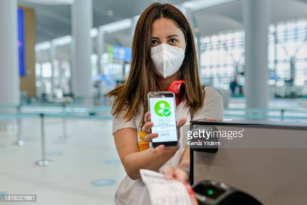 young woman traveling with her international certificate of vaccination for covid-19 - verification stock pictures, royalty-free photos & images