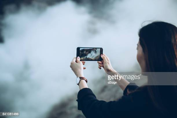 Young woman traveller capturing the spectacular view of hot spring mountain with smartphone