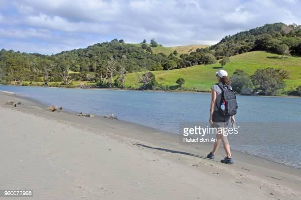 young woman traveller carrying a backpack walks along a river bank - rafael ben ari bildbanksfoton och bilder