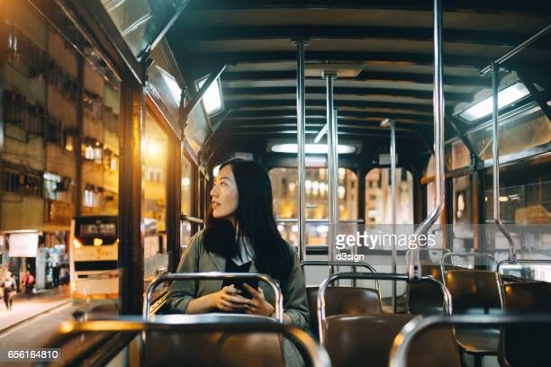 Young woman travelling on city tram and looking through window at night