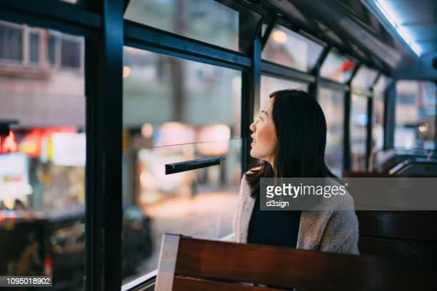 young woman travelling on city tram looking through window and enjoying the city night scene of hong kong - local landmark stock pictures, royalty-free photos & images