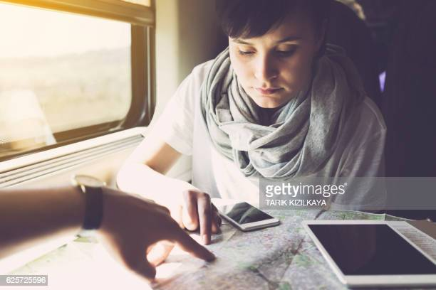 Young woman travelling, using mobile devices, inside train