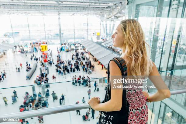 Young woman travels through airport lobby