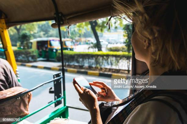 young woman travels through streets in tuk tuk - auto rickshaw stock pictures, royalty-free photos & images