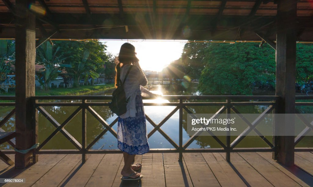 Young woman traverses bridge above tranquil river : Stock Photo