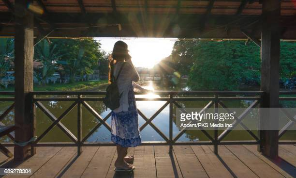 Young woman traverses bridge above tranquil river
