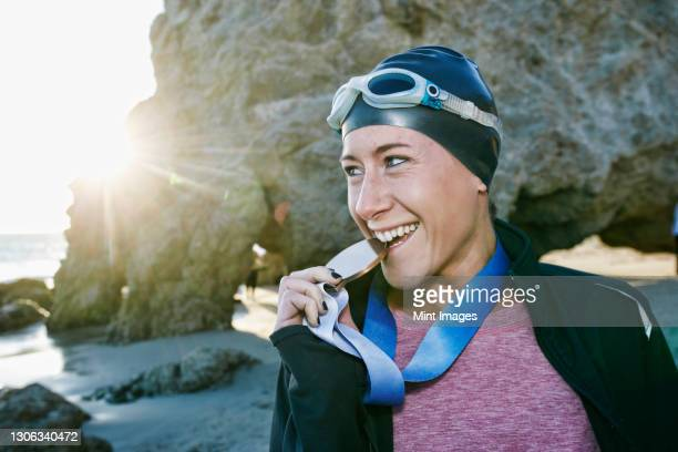 young woman, triathlete in jacket biting a large medal with her teeth, a winner - medallist stock pictures, royalty-free photos & images
