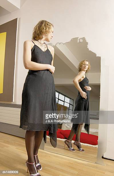 Young Woman Tries on a Black Dress Looking at Her Reflection in a Mirror
