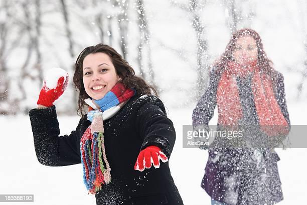 Junge Frau trowing ein Schneeball in Richtung Kamera