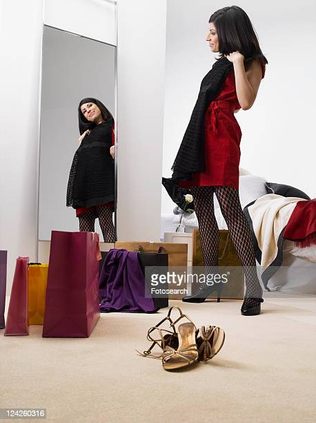 Young woman trying clothes on near mirror, low angle view
