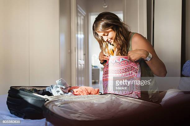 Young woman trying clothes while packing for vacation in bedroom