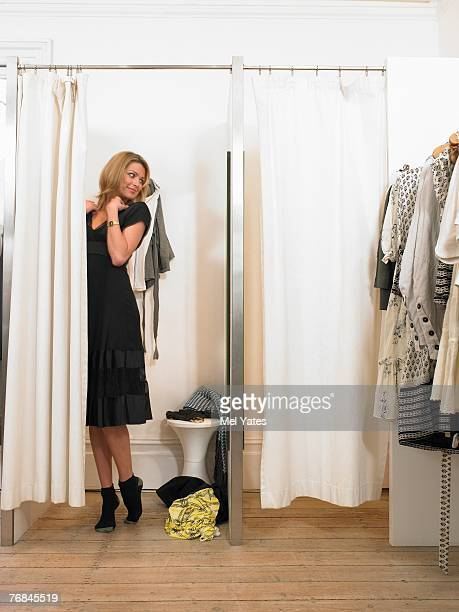 Young woman trying dress on in changing room