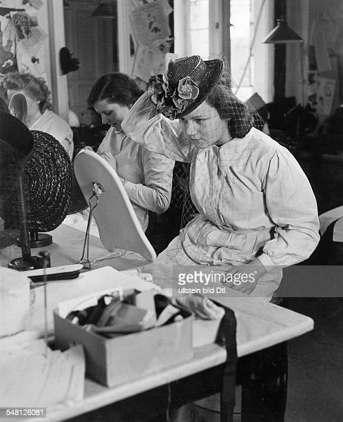 Young woman trying on a hat with veil in the salon of Berlin modiste and hatter Madame Berthe - 1941 - Photographer: Regine Relang - Published by:...