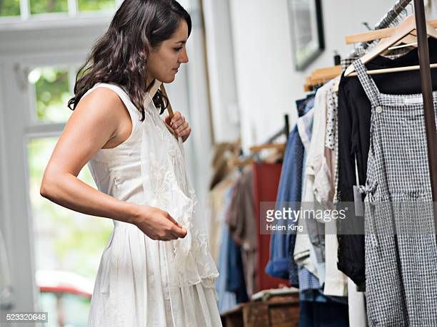 young woman trying on blouse in boutique - blouse stock pictures, royalty-free photos & images