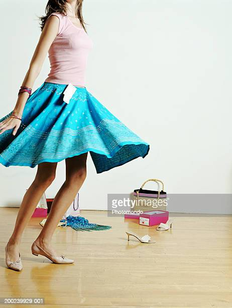 Young woman trying on clothes in shop, , twirling, mid section