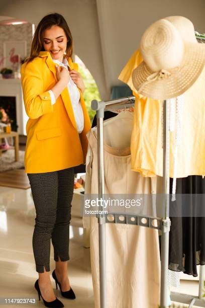 young woman trying on clothes. - jacket stock pictures, royalty-free photos & images
