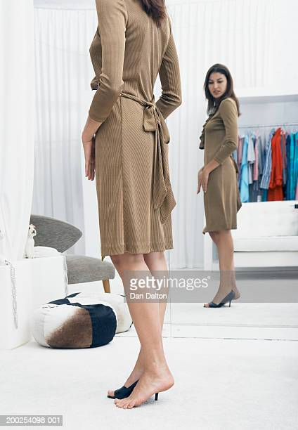 Young woman trying on dress in changing room of shop, side view