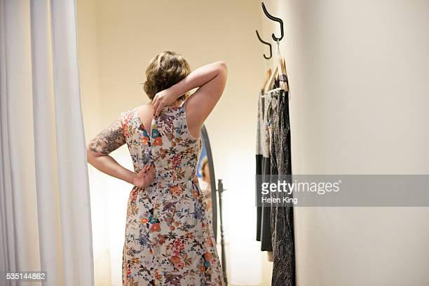 young woman trying on dress in changing room - jurk stockfoto's en -beelden