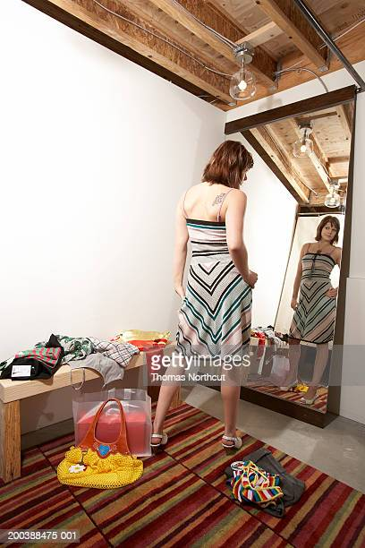 Young woman trying on dress in dressing room, hand on hip, rear view