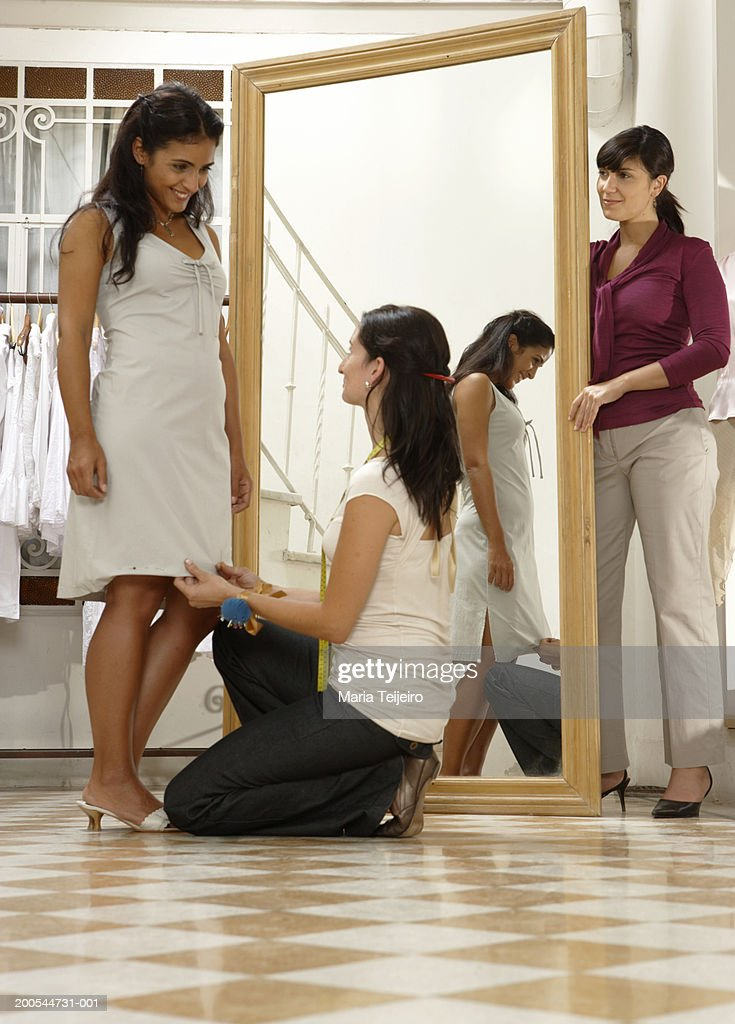 Young woman trying on dress in shop, two women assisting : Stock Photo