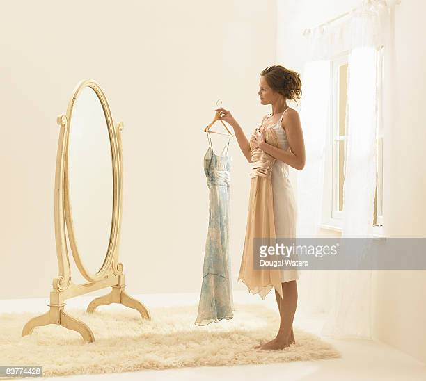 young woman trying on dresses. - beige dress stock pictures, royalty-free photos & images