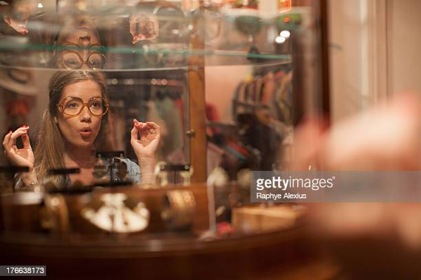 Young woman trying on glasses and pulling faces in vintage shop