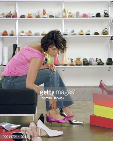young woman trying on high heels in shoe store side view