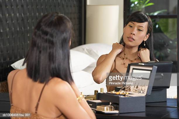Young woman trying on jewelry in mirror, rear view