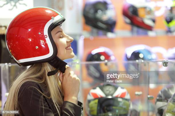 Young woman trying on motorbike helmet in shop
