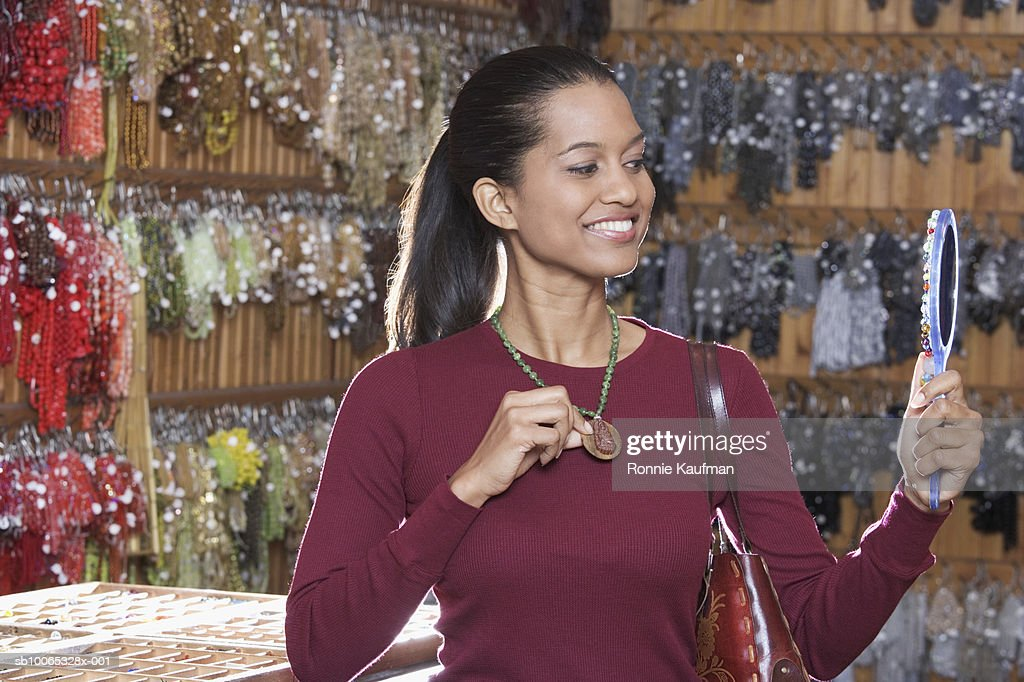Young woman trying on necklace in store, smiling : Foto stock