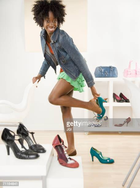 young woman trying on shoes - black purse stock pictures, royalty-free photos & images