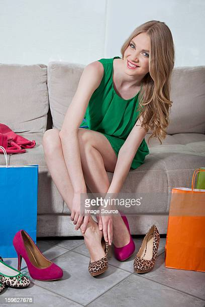 Young woman trying on shoes that she has bought