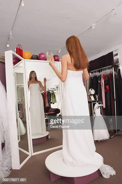 Young woman trying on wedding dress, looking in mirror