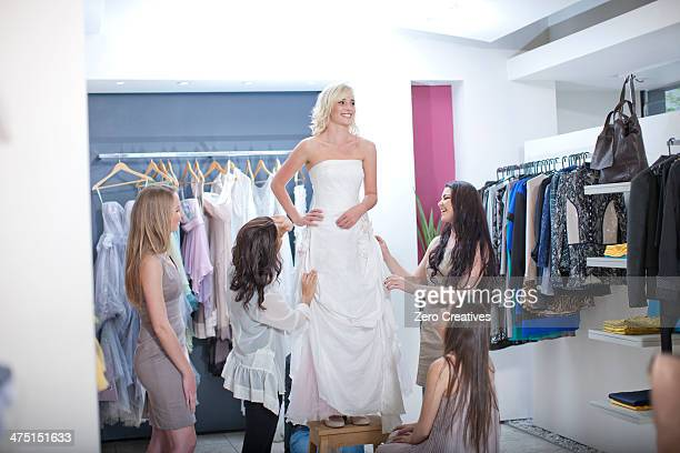 Young woman trying on wedding dress, with friends