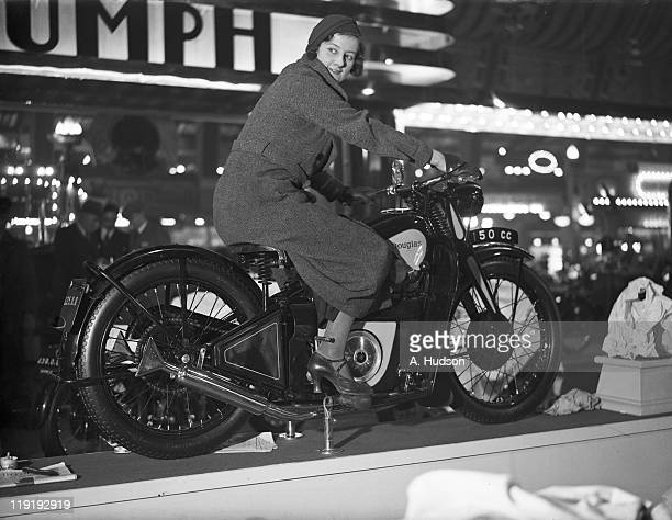 Young woman trying out a Douglas motorcycle on display at the 18th Cycle and Motorcycle Show at Olympia, London, 25th November 1933.