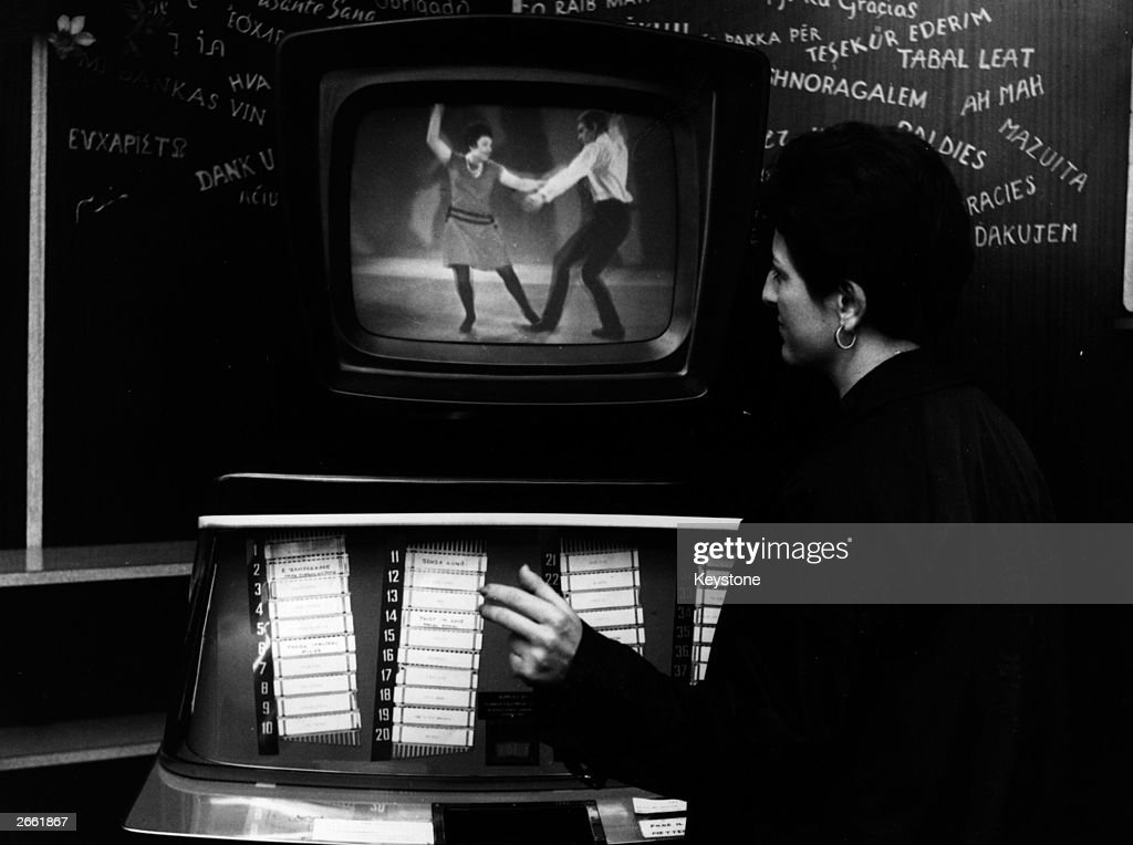 A young woman trying out the 'Cinebox', which combines a jukebox with a colour television.