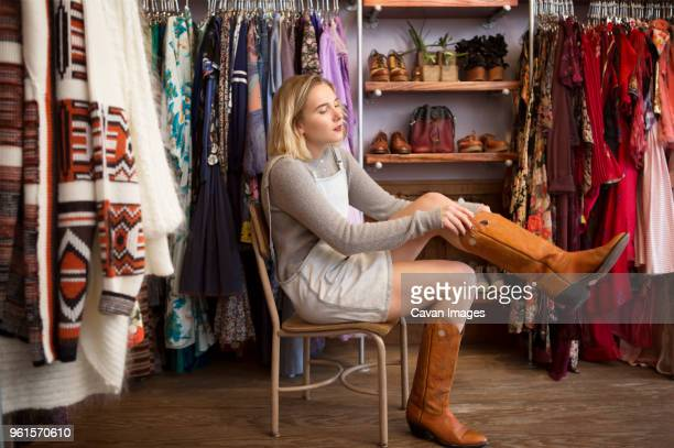 young woman trying rubber boots in boutique - boot stock pictures, royalty-free photos & images