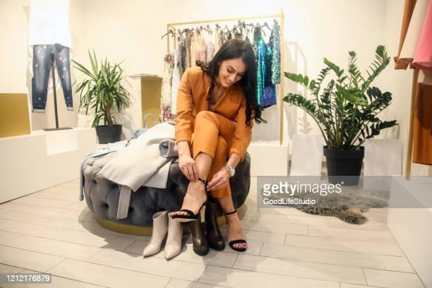 jovem mulher experimentando sapatos em - sapato - fotografias e filmes do acervo