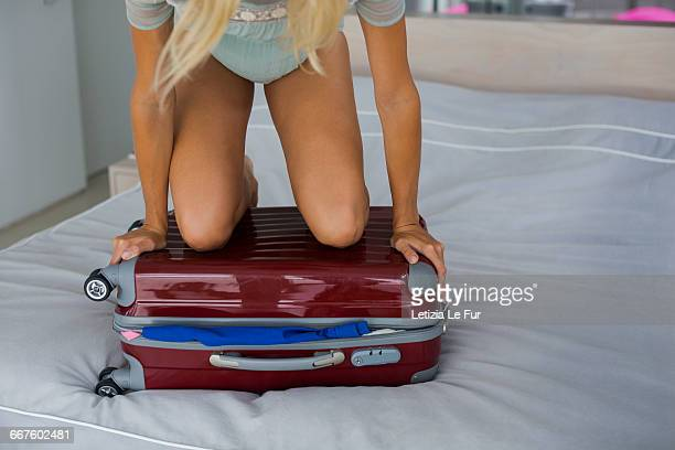 Young woman trying to close overflow suitcase