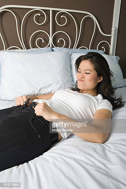 Young woman trying to do up her jeans