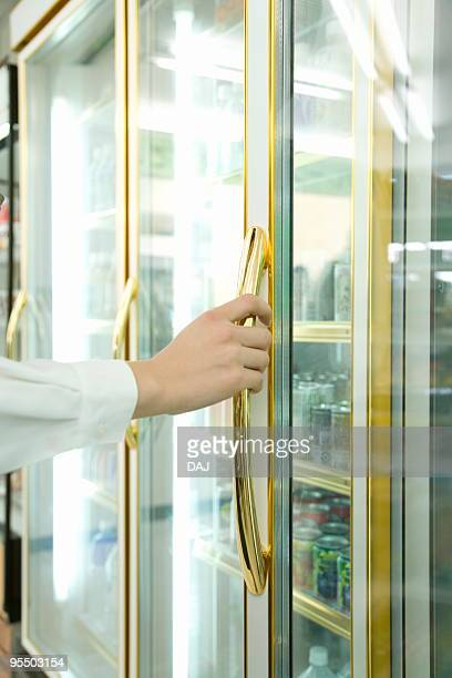 Young woman trying to open the refrigerator
