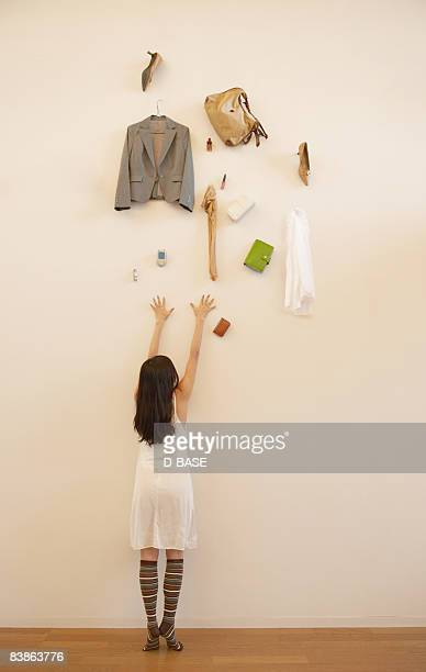 Young woman trying to reach her items from  wall