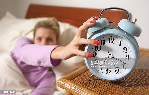 Young woman turning off alarm