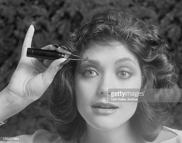 Young woman tweezing eyebrows, close-up