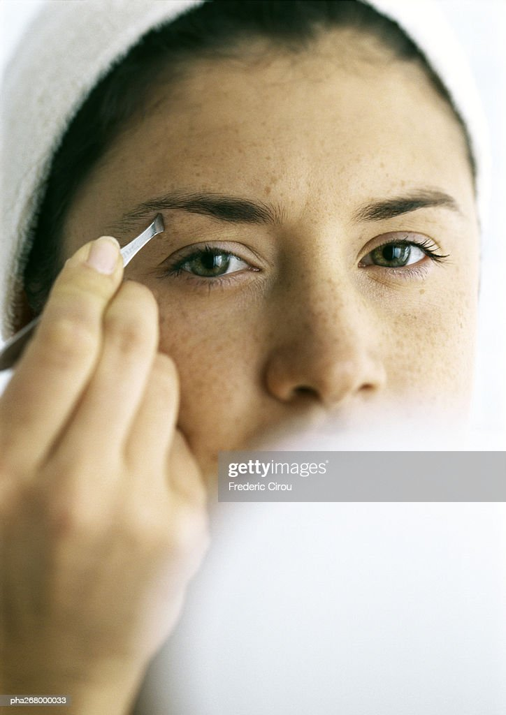 Young woman tweezing eyebrows, compact blurred in foreground : Stockfoto
