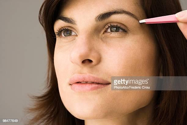 Young woman tweezing eyebrows