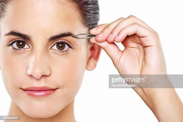 Young Woman Tweezing Her Eyebrows