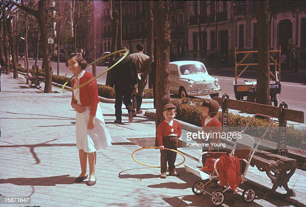 A young woman twirls a hulahoop around her neck while her charges two small children watch Madrid Spain 1960s or 1970s