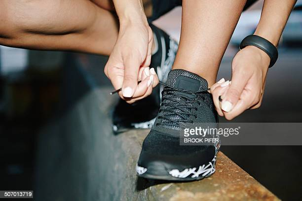 young woman tying athletic shoelace - sapato preto - fotografias e filmes do acervo
