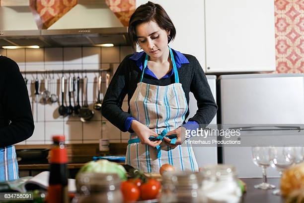 Young woman tying her apron in cooking class